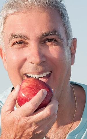 older man with implant dentures in Costa Mesa biting an apple