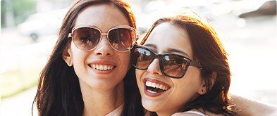 two girls smiling with sunglasses on