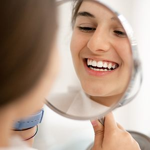 teen smiling into mirror