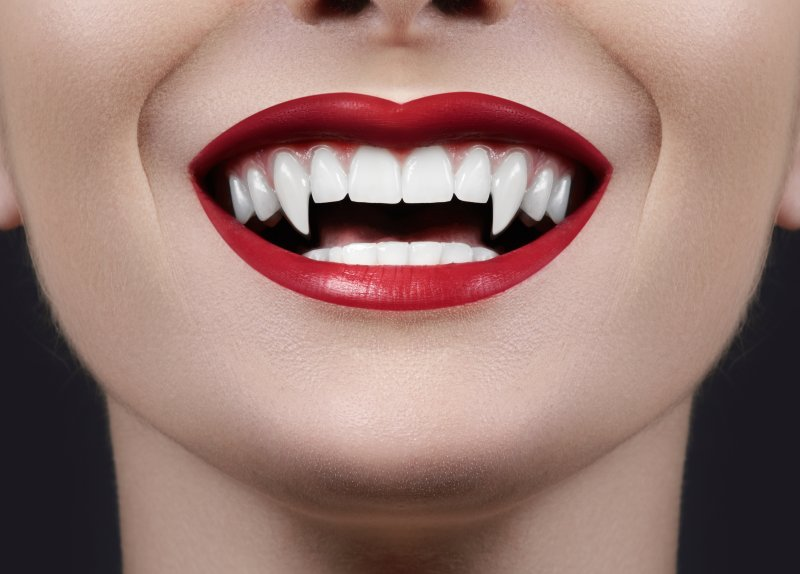 girl smiling with vampire fangs from tiktok trend