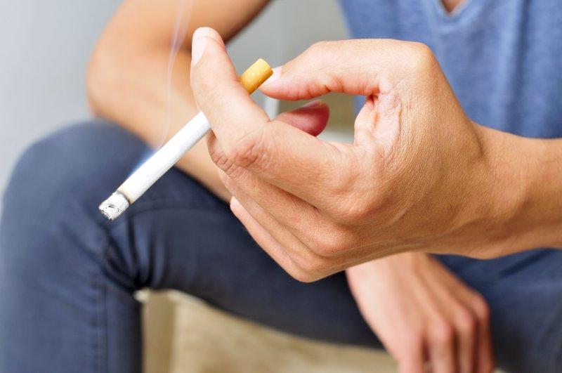 Closeup of man holding a cigarette